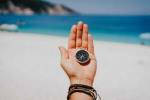 Stretched hand palm with black metal compass against summer beach and blue sea. Follow your way